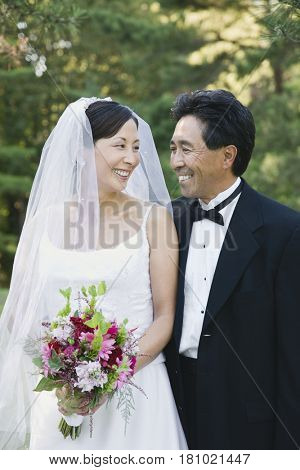 Asian newlyweds smiling at each other
