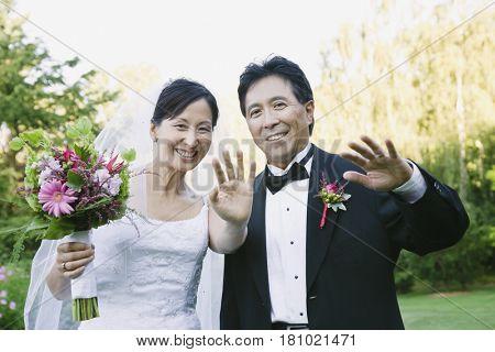 Asian newlyweds waving