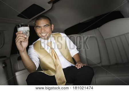 Asian man holding drink in limousine