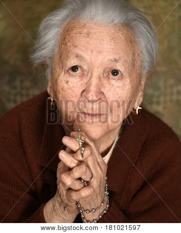 Old Woman Praying And  Holding Silver Rosary