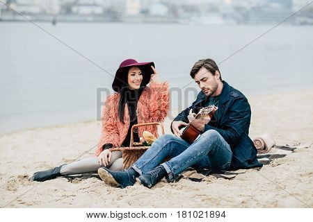 Man Playing Guitar At Alfresco Picnic