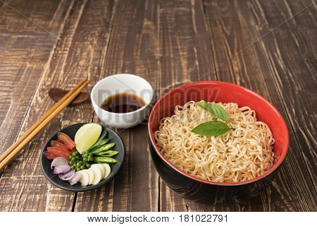 Noodles with sauce or shoyu and ingredient on table wood backgroound in close up.