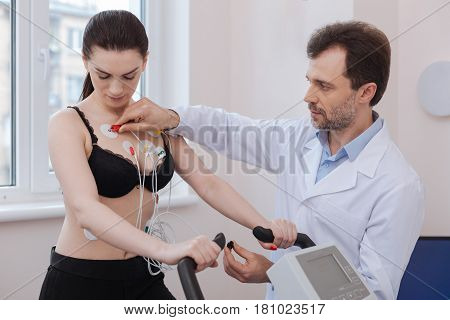 Completing verification. Wonderful attentive young specialist checking the connection of the sensors before starting a test for examining his patients cardiovascular system