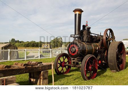 WESTERNHANGER, UK - JULY 21: A vintage steam engine stands alongside a wood cutting bench as part of the vintage machinery display at the War & Peace Revival show on July 21, 2016 in Westernhanger