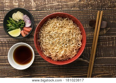 noodles with shoyu or sauce and ingredient on wood backgroound top view