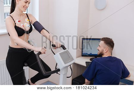 I can do more. Motivated charming young lady feeling great while doing some exercises and the doctor examining her performance results
