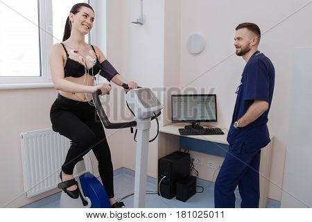 Pleasant science. Excited active beautiful woman performing some cardio exercises while the doctor examining her results and making conclusions