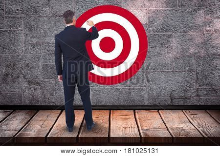 Digital composite of Rear view of businessman standing in front of bull's eye