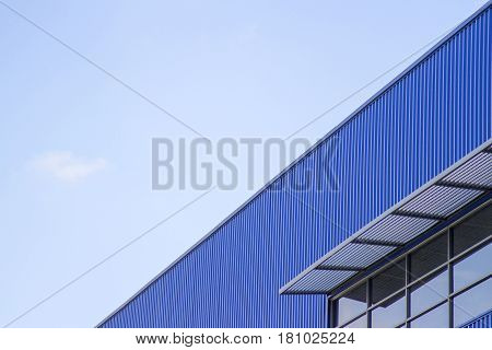 Building of blue wall and window mirror on blue sky