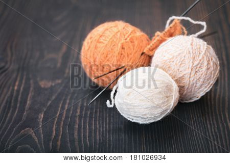Skeins of wool thread for knitting on a wooden background.