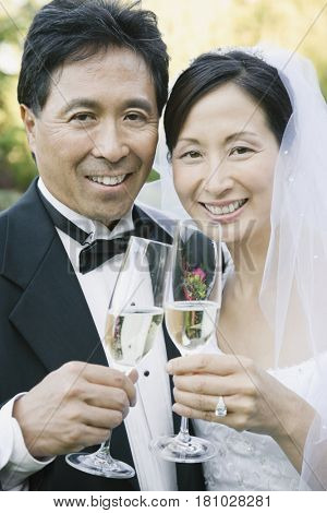 Asian newlyweds toasting with champagne