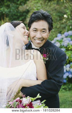 Asian newlyweds hugging