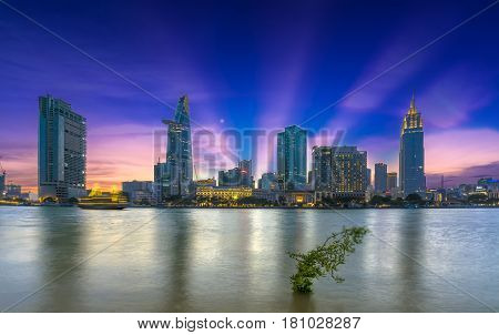 Ho Chi Minh City, Vietnam - March 25th, 2017: Riverside City sunrays clouds in the sky at end of day brighter coal sparkling skyscrapers along beautiful river in Ho Chi Minh City, Vietnam