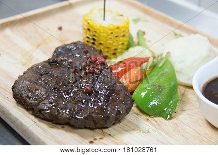 A grilled ribeye steak with baked potato and vegetables.