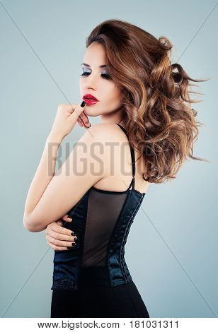 Perfect Woman with Long Wavy Hair. Alluring Fashion Model with Curly Hairstyle and Makeup