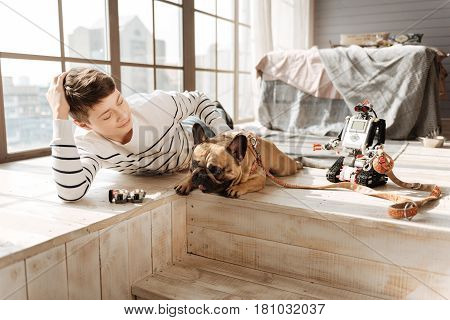 Stay at home. Positive delighted boy patting his dog that is lying between robot and boy, being ready for a walk