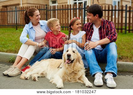 Affectionate family having rest on lawn by their house