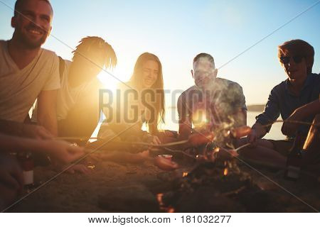 Group of cheerful campers roasting sausages on the beach