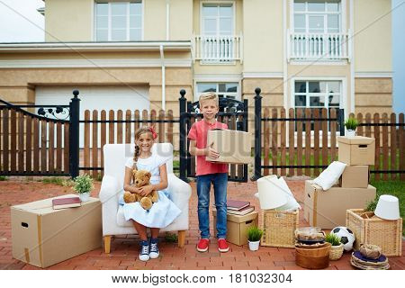 Cute boy with box and his sister helping parents to relocate