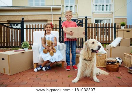 Two happy kids and their pet during relocation