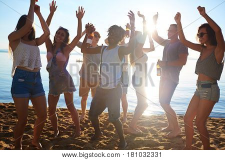 Group of ecstatic guys and girls ancing on sand