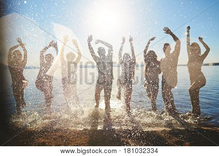 Row of friends raising hands while splashing water on sunny day