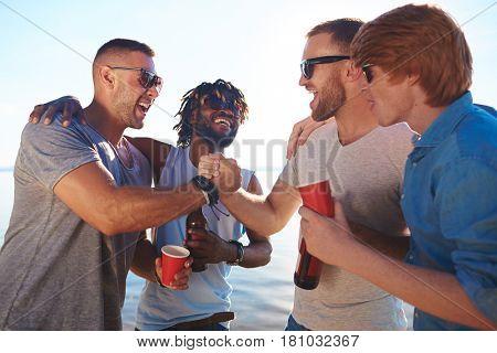 Friendly guys having fun on summer weekend by seaside