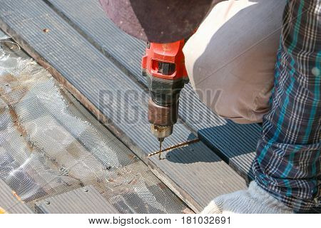 Carpenter Hand Or Hand Of Worker Drills A Hole With Wooden Plank Using Electric Drell Machine In Wor