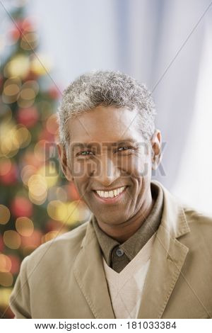 African man in front of Christmas tree