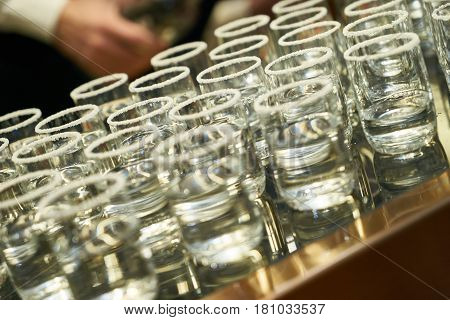 Unhealthy food and drinks. Drink set of tequila glasses with yellow beverage on bar counter. Alcohol drinks. Close-up