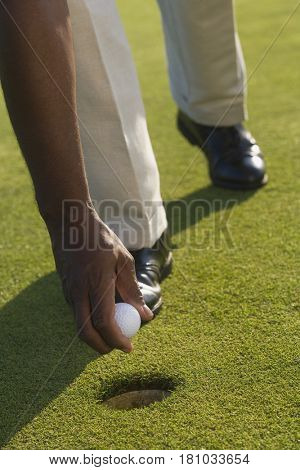 African man picking up golf ball