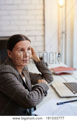 Aged businesswoman having minute of rest