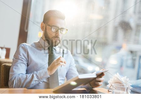 Serious man with pen and notebook concentrating on his thoughts