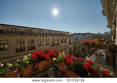 Beautiful landscape design of urban buildings. View from the veranda decorated with flowers against the blue sky and the sun on a warm spring day