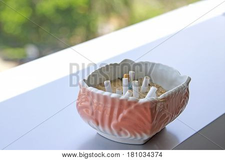 The pink ashtray is placed on the table.