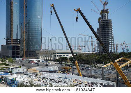 Huge crane and construction plant. Big construction crane and the building against the sky background. Tower Crane in Construction site.