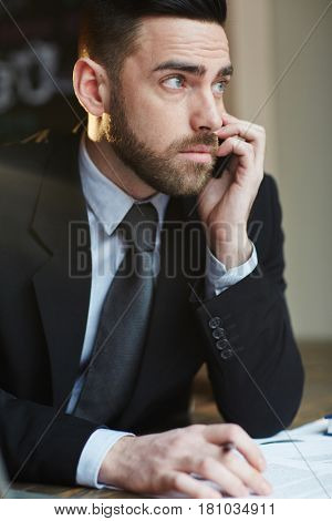 Portrait of modern bearded businessman making phone call while working in office at desk