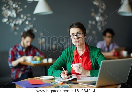 Young creative businesswoman wearing glasses and colorful casual clothes looking at camera while working with magazines and laptop at table in cafe, two other people in background