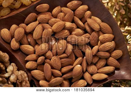 Close-up of Almonds in a brown bowl on wooden background. Almond kernels