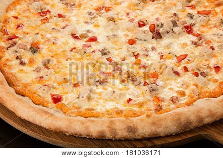 Pizza Spicy, spicy sauce, mozzarella, bacon, chicken, bell peppers, Parmesan on a black background