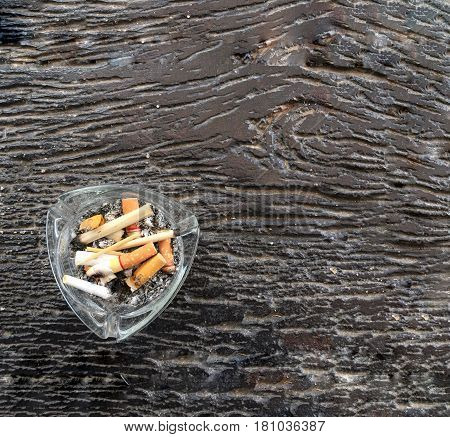 Smokers ashtray on brown wood background top view