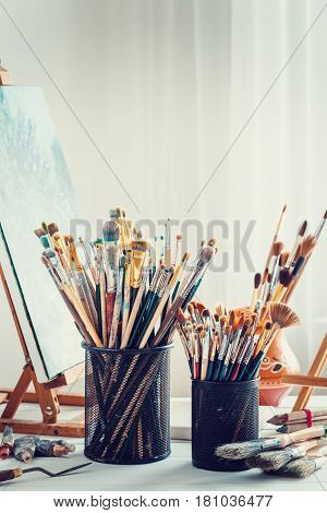 Artistic Equipment In Studio Of Painter: Wooden Easel,  Paintbrushes, Tubes Of Paint, Palette And Pa