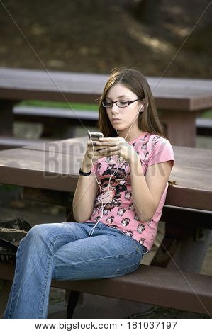 Hispanic girl listening to mp3 player