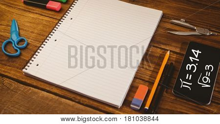 Digital composite of High angle view of spiral formula in digital tablet by noptebook and school supplies on wooden table