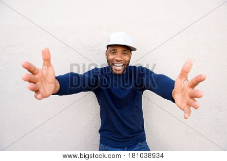 Cheerful Young African Man With Arms Outstretched By Wall
