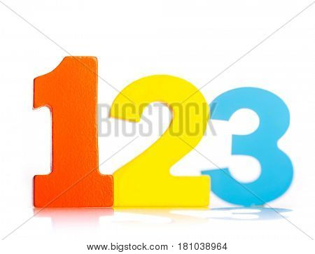 Colorful wooden toy numbers one two three on white background focus on the 1
