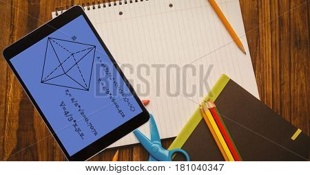 Digital composite of Overhead view of diagram with formula in digital tablet on book at table