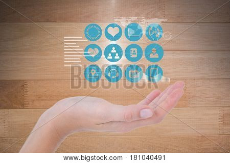 Digital composite of Digitally generated image of various icons over hand against wooden wall