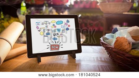 Digital composite of Various icons and text in digital tablet by basket and paper on table