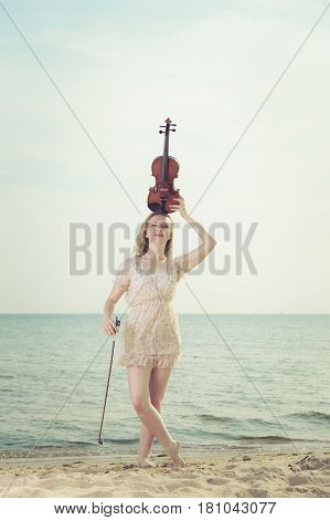 Music love hobby and everyday passion concept. Woman on beach near sea having violin on head
